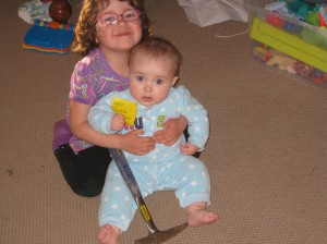 picture of two girls with rock hammer for scale